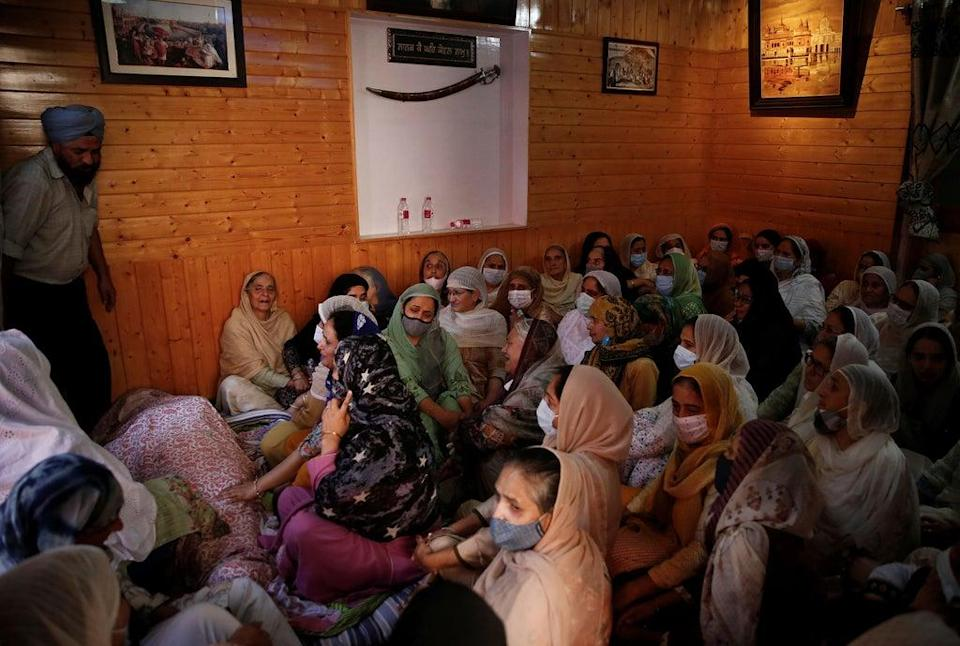 Relatives mourn around the body of Supinder Kour, a school teacher, who was shot and killed by suspected militants in Srinagar (REUTERS)