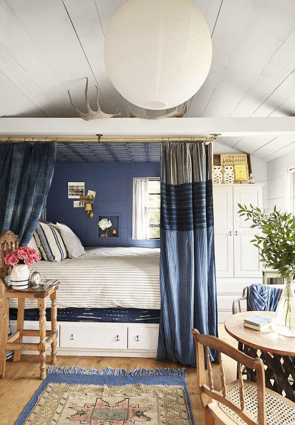 """<p>Use paint to create a cozy bed nook within a bigger bedroom. The second homeowner Matt Albiani of <a href=""""https://www.mategallery.com/"""" rel=""""nofollow noopener"""" target=""""_blank"""" data-ylk=""""slk:Mate Gallery"""" class=""""link rapid-noclick-resp"""">Mate Gallery</a> walked into the cozy (only about 12 feet by 15 feet!) freestanding art studio, he envisioned a captain's bed, but it took his partner Ron Brand a little longer to """"see it."""" Says Ron, """"I needed a couple of glasses of wine and <em>a lot</em> of tape on the floor, and then the penny dropped!"""" Once the bed was built, they hung the indigo textiles and added indigo-inspired wallpaper on the wall and ceiling.<strong><br></strong><strong><br></strong><strong>Get the Look: <br></strong>Blue Wall Paint Color: <a href=""""https://store.benjaminmoore.com/storefront/index.ep"""" rel=""""nofollow noopener"""" target=""""_blank"""" data-ylk=""""slk:New York State of Mind by Benjamin Moore"""" class=""""link rapid-noclick-resp"""">New York State of Mind by Benjamin Moore<br></a>Ceiling Wallpaper: <a href=""""https://go.redirectingat.com/?id=74968X1525072&xs=1&url=https%3A%2F%2Fwww.serenaandlily.com%2Fgranada-wallpaper%2Fm12427.html&sref=https%3A%2F%2Fwww.countryliving.com%2Fhome-design%2Fhouse-tours%2Fg32026876%2Fhamptons-beach-cottage%2F%3Fpre%3Dhome-design%252Fhouse-tours%252F%26prefix%3Dg%26id%3D32026876%26del%3D%26variantId%3D%26post%3D%252Fhamptons-beach-cottage"""" rel=""""nofollow noopener"""" target=""""_blank"""" data-ylk=""""slk:Granada; serenaandlily.com"""" class=""""link rapid-noclick-resp"""">Granada; <em>serenaandlily.com<br></em></a>Indigo textiles, ceramic owls, and vintage accessories: <em><a href=""""https://www.mategallery.com/"""" rel=""""nofollow noopener"""" target=""""_blank"""" data-ylk=""""slk:mate"""" class=""""link rapid-noclick-resp""""><em>mate</em></a></em><em><em><a href=""""https://www.mategallery.com/"""" rel=""""nofollow noopener"""" target=""""_blank"""" data-ylk=""""slk:gallery.com"""" class=""""link rapid-noclick-resp"""">gallery.com</a></em></em></p>"""