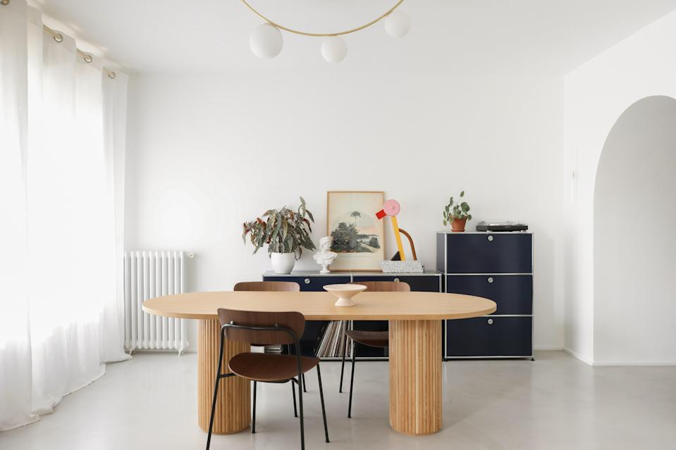 """<div class=""""caption""""><strong>AFTER:</strong> In the dining room, <a href=""""https://www.andtradition.com/products/pavilion-av2"""" rel=""""nofollow noopener"""" target=""""_blank"""" data-ylk=""""slk:&Tradition chairs"""" class=""""link rapid-noclick-resp"""">&Tradition chairs</a> surround the made-to-measure table by Heju with an <a href=""""http://www.atelierareti.com/pendant-lamps-2/girlande-ceiling"""" rel=""""nofollow noopener"""" target=""""_blank"""" data-ylk=""""slk:Atelier Areti ceiling light"""" class=""""link rapid-noclick-resp"""">Atelier Areti ceiling light</a> above it. A <a href=""""https://artemest.com/products/tahity-table-lamp-by-ettore-sottsass"""" rel=""""nofollow noopener"""" target=""""_blank"""" data-ylk=""""slk:Ettore Sottsass table lamp"""" class=""""link rapid-noclick-resp"""">Ettore Sottsass table lamp</a> sits on the <a href=""""https://www.usm.com/en-us/modern-home/inspiration/applications/shelving/"""" rel=""""nofollow noopener"""" target=""""_blank"""" data-ylk=""""slk:USM shelves"""" class=""""link rapid-noclick-resp"""">USM shelves</a>.</div>"""