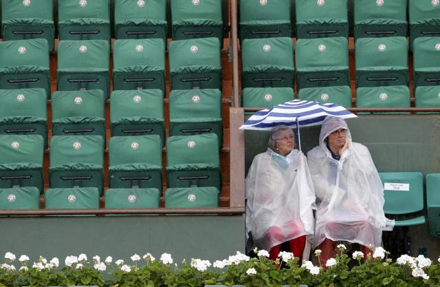 Spectators protect themselves from the rain with umbrella before the start of the women's quarter-final match between Sara Errani of Italy and Andrea Petkovic of Germany during the French Open tennis tournament at the Roland Garros stadium in Paris June 4, 2014. REUTERS/Jean-Paul Pelissier (FRANCE - Tags: SPORT TENNIS ENVIRONMENT)