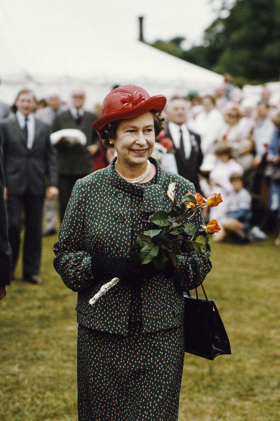 <p>The queen looked marvelous in a green printed suit with flares of orange and white during the Sandringham Flower Show in Sandringham, Norfolk.<br></p>