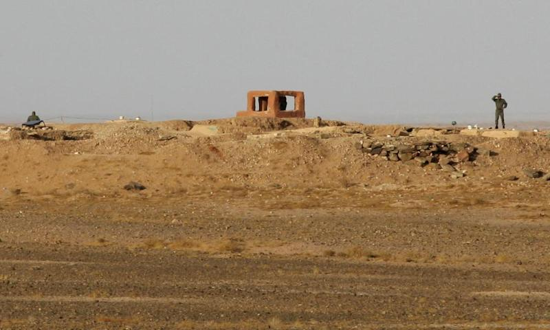 Soldiers from the Moroccan army stand behind a fortified earthwork on the Berm.