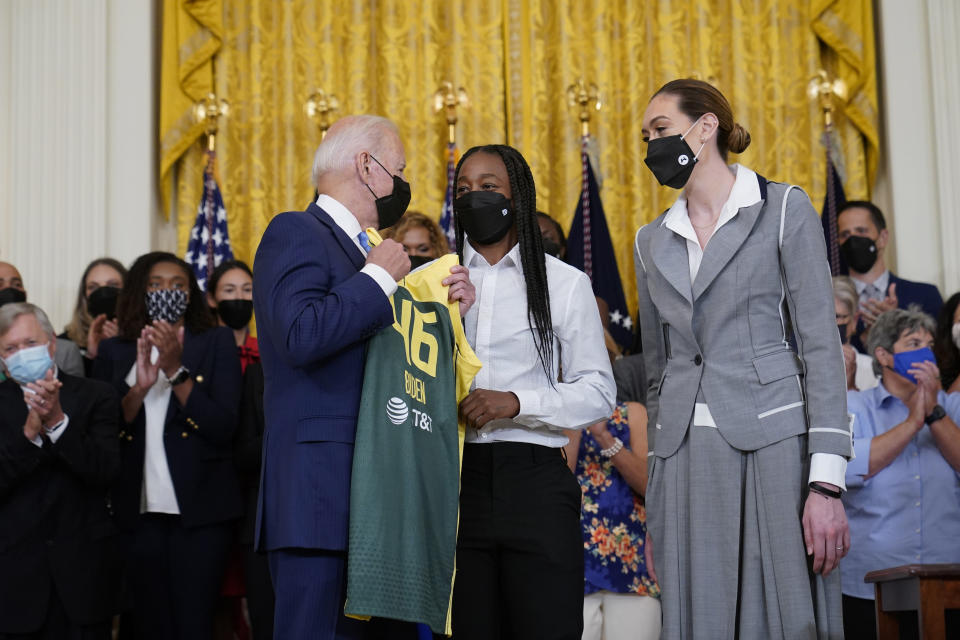 President Joe Biden, left, talks with Seattle Storm's Jewell Loyd, center, and Breanna Stewart, right, during an event in the East Room of the White House in Washington, Monday, Aug. 23, 2021, to celebrate their 2020 WNBA Championship. (AP Photo/Susan Walsh)