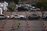 A National Guardsman walks across a federally-run COVID-19 vaccination site as motorists wait to get their vaccine on the campus of California State University of Los Angeles in Los Angeles, Calif., Tuesday, Feb. 16, 2021. (AP Photo/Jae C. Hong)