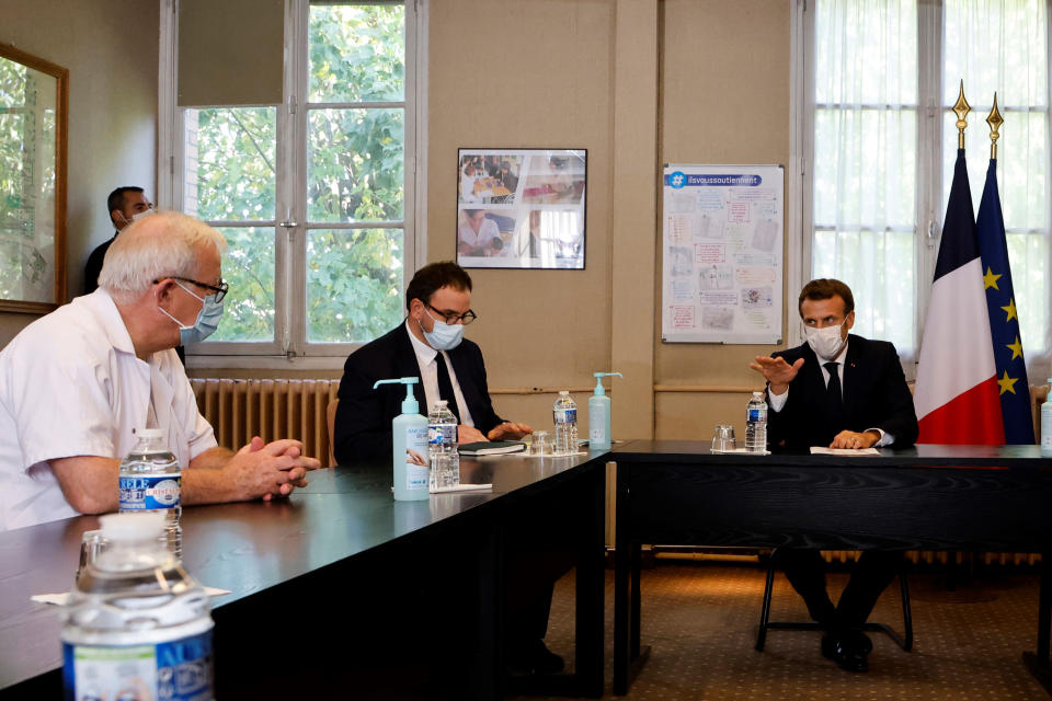 "French President Emmanuel Macron, right, chairs a meeting with the medical staff of the Rene Dubos hospital center, in Pontoise, outside Paris, Friday Oct. 23, 2020. French Prime Minister Jean Castex said Thursday a vast extension of the nightly curfew that is intended to curb the spiraling spread of the coronavirus, saying ""the second wave is here."" The curfew imposed in eight regions of France last week, including Paris and its suburbs, is being extended to 38 more regions and Polynesia, (Photo by Ludovic Marin, Pool via AP)"