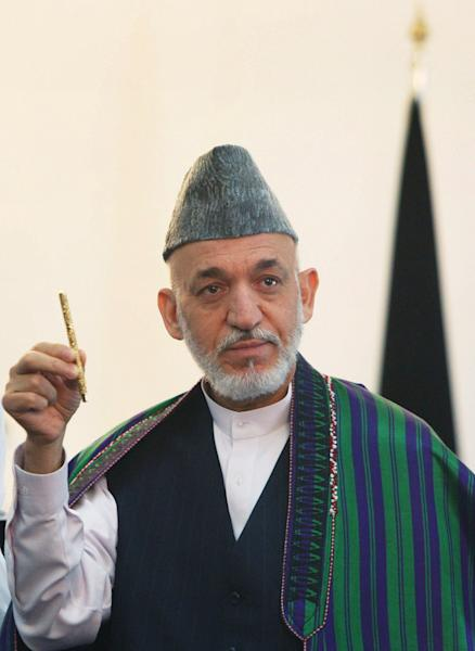 Afghan President Hamid Karzai holds a pen which belonged to former Afghanistan King Shah Amanullah Khan, who ruled the country from 1919, to 1929, during a ceremony where he received the pen from the King's daughter, Princess India of Afghanistan, at the presidential palace in Kabul, Afghanistan, Monday, Aug. 27, 2012. The pen will be transferred to the Afghan National Museum. (AP Photo/Ahmad Massoud /Xinhua, Pool)
