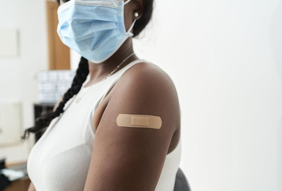 Black woman with braid in her hair with white shirt and mask showing the band-aid on her arm after vaccination, with white background. Concept of covid