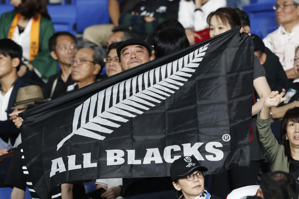 FILE - In this Sept. 21, 2019, file photo, a New Zealand fan holds an All Blacks flag and cheers for his team ahead of the start of the Rugby World Cup Pool B game between New Zealand and South Africa in Yokohama, Japan. New Zealand Rugby will make an emergency grant of $150,000 to each of its five Super Rugby teams to help them weather the next three months while the southern hemisphere tournament is suspended because of the global pandemic. (AP Photo/Shuji Kajiyama)