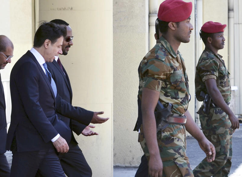Italy's Prime Minister Giuseppe Conte, left, is welcomed by Ethiopia's Prime Minister Abiy Ahmed, second from left, upon his arrival at the airport in Addis Ababa, Ethiopia Thursday, Oct. 11, 2018. The two parties will have bilateral discussions on trade, investment, and other matters according to Ethiopia's Prime Minister's office. (AP Photo)