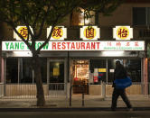 A man walks past the outside of Yang Chow restaurant at night in Los Angeles, Thursday, Dec. 17, 2020. Bigotry toward Asian Americans and Asian food has spread steadily alongside the coronavirus in the United States. Yun said even though his businesses have survived the pandemic, they get prank calls almost daily asking if they have dog or cat on the menu or impersonating a thick Asian accent. (AP Photo/Damian Dovarganes)