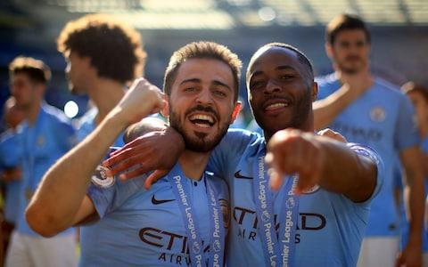 Bernardo Silva and Raheem Sterling of Manchester City celebrate after winning the title following the Premier League match between Brighton & Hove Albion and Manchester City - Credit: Tom Flathers/Manchester City FC