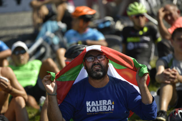 Spanish La Vuelta fans protect himself of the sun with a basque flag next to the finish line during the 17th stage between Getxo and Balcon de Vizcaya, 157 kilometers (97,55miles), of the Spanish Vuelta cycling race that finishes in Balcon de Vizcaya, northern Spain, Wednesday, Sept. 12, 2018. (AP Photo/Alvaro Barrientos)