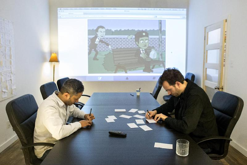 In this Dec. 19, 2013 photo, Bitstrips CEO and Creative Director Jacob Blackstock, right, and co-founder Shahan Panth draw cartoons as part of a brain storming process at the company's offices in Toronto. Bitstrips, a mobile application that helps people turn their lives into comic strips, may seem like a sudden sensation now that its vignettes are all over Facebook and other social networks. But the Toronto startup's success has been a drawn-out process. (AP Photo/The Canadian Press, Chris Young)
