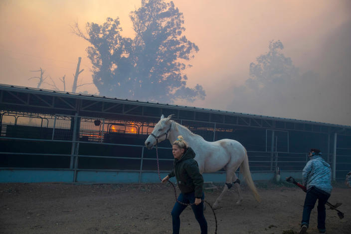 A woman flees Castle Rock Farms with her horse as the Easy fire approaches October 30, 2019 in Simi Valley, California. Fueled by the Santa Ana winds, the fire has quickly spread to 1300 acres. (Photo: Brian van der Brug/Los Angeles Times via Getty Images)