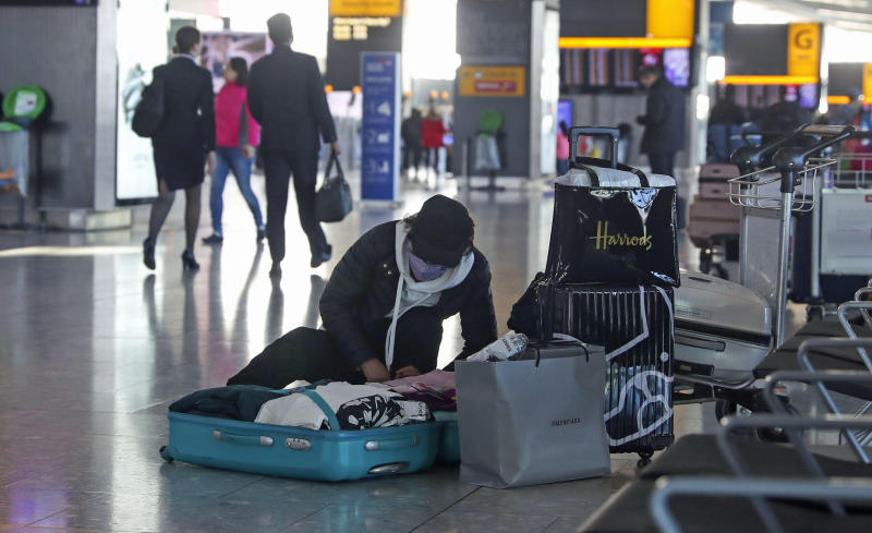 A woman wearing a face mask packs her suitcase in the departures area of Terminal 5 at Heathrow Airport, after it was announced British Airways has suspended all services to and from China. (Photo by Steve Parsons/PA Images via Getty Images)