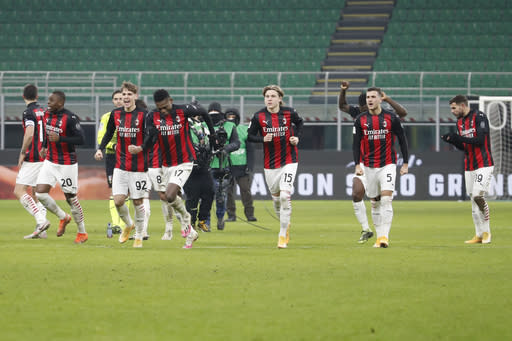 AC Milan players celebrate after defeating Torino in their Italian Cup round of 16 soccer match between AC Milan and Torino at the San Siro stadium, in Milan, Italy, Tuesday, Jan. 12, 2021. (AP Photo/Antonio Calanni)