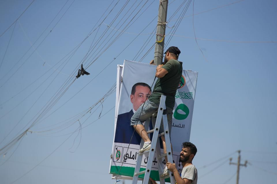 Men place an election poster for the upcoming early parliamentary elections near private generator network wires in Baghdad, Iraq, Monday, Sept. 20, 2021. In Iraq, electricity is a potent symbol of endemic corruption, rooted in the country's sectarian power-sharing system. It's perpetuated after each election cycle: Once results are tallied, politicians jockey for appointments in a flurry of negotiations based on the number of seats won. (AP Photo/Hadi Mizban)