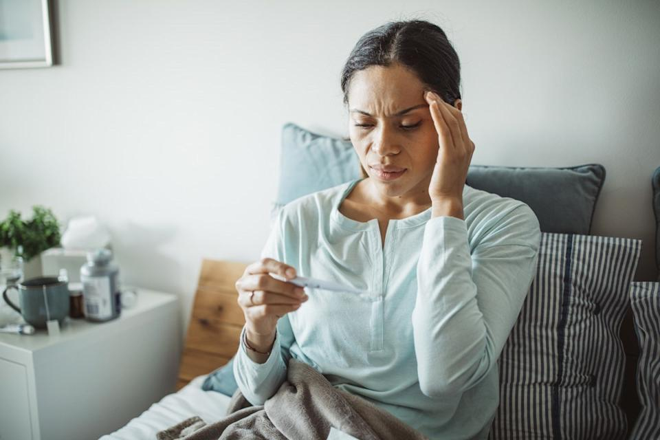 Woman with flu in bed, she use thermometer to measure temperature