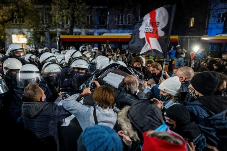 Protestors scuffle with riot police guarding the house of Jaroslaw Kaczynski, leader of Poland's ruling Law and Justice party (PIS)