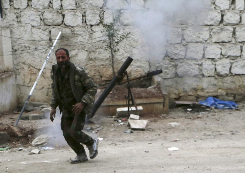 A Free Syrian Army fighter reacts after launching a mortar towards forces loyal to Syria's President Bashar al-Assad in Karm al-Tarab neighborhood in Aleppo February 10, 2014. REUTERS/Hosam Katan (SYRIA - Tags: POLITICS CIVIL UNREST CONFLICT)