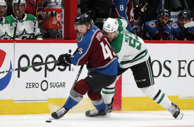 Colorado Avalanche defenseman Bowen Byram, left, fights for control of the puck with Dallas Stars left wing Michael Mersch in the second period of an NHL preseason hockey game Thursday, Sept. 19, 2019, in Denver. (AP Photo/David Zalubowski)