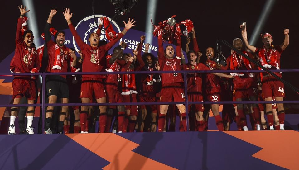 FILE - In this July 22, 2020, file photo, Liverpool's Jordan Henderson lifts the English Premier League trophy following their soccer match against Chelsea at Anfield Stadium in Liverpool, England. (Laurence Griffiths/Pool Photo via AP, File)
