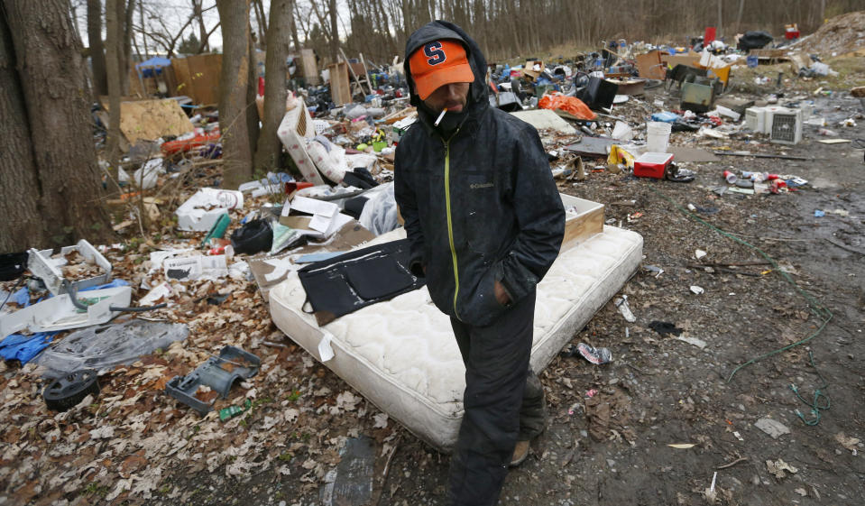 Chris Hartman walks through the homeless encampment, known as the Jungle, where he lives in Ithaca, N.Y., Monday, Dec. 7, 2020. The pandemic has caught homeless service providers in a crosscurrent: demand is high, but their ability to provide services are constricted. (AP Photo/John Munson)