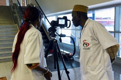 Health workers set up a thermal scanner to screen arriving passengers at Dakar's international airport