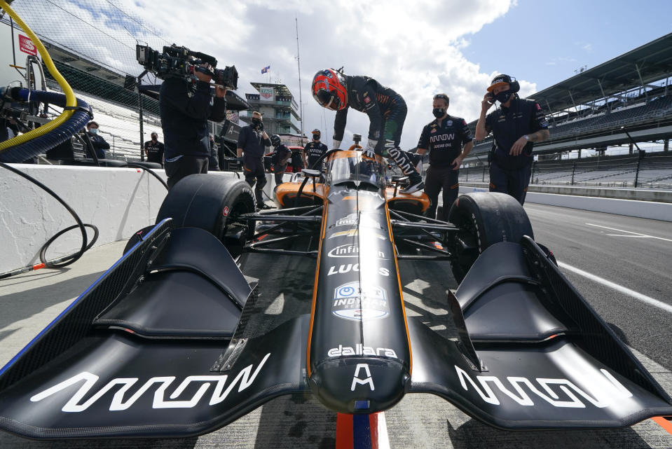 Helio Castroneves, of Brazil, climbs into his car during a practice session for an IndyCar auto race at Indianapolis Motor Speedway, Thursday, Oct. 1, 2020, in Indianapolis. (AP Photo/Darron Cummings)