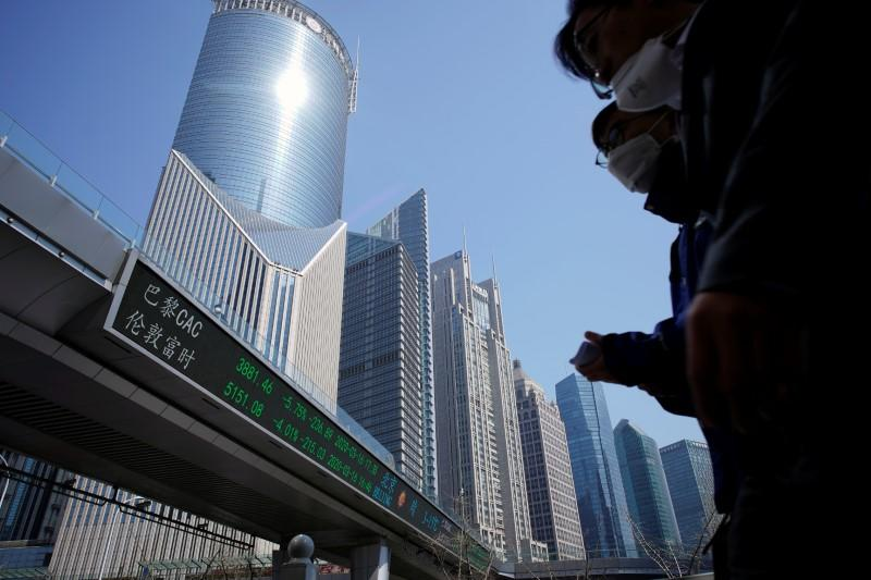 Pedestrians wearing face masks walk near an overpass with an electronic board showing stock information in Shanghai