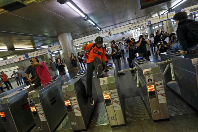 A protester jumps over closed gates inside Ana Rosa subway station during the fifth day of metro worker's protest in Sao Paulo June 9, 2014. Brazilian police used tear gas on Monday to disperse metro workers on strike in Sao Paulo in defiance of a court order to return to work, causing major traffic congestion just three days before the city hosts the opening match of the World Cup soccer tournament. REUTERS/Kai Pfaffenbach (BRAZIL - Tags: BUSINESS EMPLOYMENT SOCCER SPORT TRANSPORT CIVIL UNREST WORLD CUP)