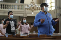 """Parishioners wearing masks as a measure to prevent the spread of COVID19 pray during a Mass at the Our Lady of Consolation Parish on Sunday, Aug. 2, 2020, in Quezon city, Philippines. Coronavirus infections in the Philippines continues to surge Sunday as medical groups declared the country was waging """"a losing battle"""" against the contagion and asked the president to reimpose a lockdown in the capital. (AP Photo/Aaron Favila)"""