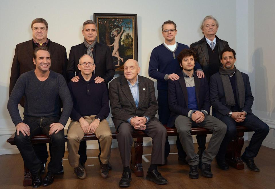 Cast members of the film The Monuments Men pose during a photocall in front of 'Cupid Complaining To Venus', by Lucas Cranach the Elder, believed to be from Adolf Hitler's private collection, at the National Gallery, in London, Tuesday, Feb. 11, 2014. From left to right seated, French actor Jean Dujardin, US actor Bob Balaban, real life 'monument man' Harry Ettlinger , British actor Dimitri Leonidas and US actor Grant Heslov. In background from left to right, US actors, John Goodman, George Clooney, Matt Damon and Bill Murray. (Photo by Jon Furniss/Invision/AP)