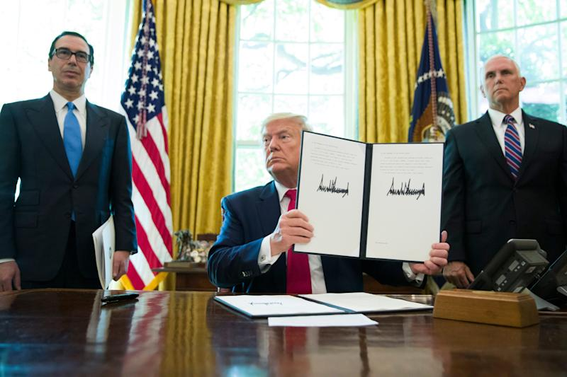 President Donald Trump holds up a signed executive order to increase sanctions on Iran, accompanied by Treasury Secretary Steve Mnuchin, left, and Vice President Mike Pence, in the Oval Office on June 24, 2019.