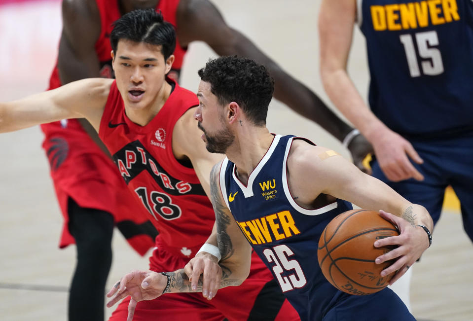 Denver Nuggets guard Austin Rivers, front, is defended by Toronto Raptors forward Yuta Watanabe during the first half of an NBA basketball game Thursday, April 29, 2021, in Denver. (AP Photo/David Zalubowski)