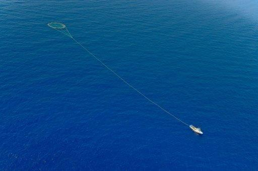 A tuna fishing boat is seen dragging a cage of nets