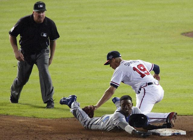 As umpire Mike Muchlinski, left, watches, Los Angeles Dodgers' Dee Gordon, bottom right, tries to steal second base as Atlanta Braves shortstop Andrelton Simmons (19) makes the tag in the ninth inning of Game 2 of the National League division series on Friday, Oct. 4, 2013, in Atlanta. The Braves won 4-3. (AP Photo/Dave Martin)