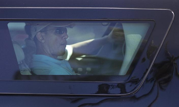 President Barack Obama is seen through the window of his motorcade vehicle as he is driven through the Kailua, Hawaii, neighborhood where he is spending his annual holiday vacation with his family, Tuesday, Dec. 24, 2013, en route to Marine Corps Base Hawaii in Kaneohe, Hawaii, to play golf. (AP Photo/Carolyn Kaster)