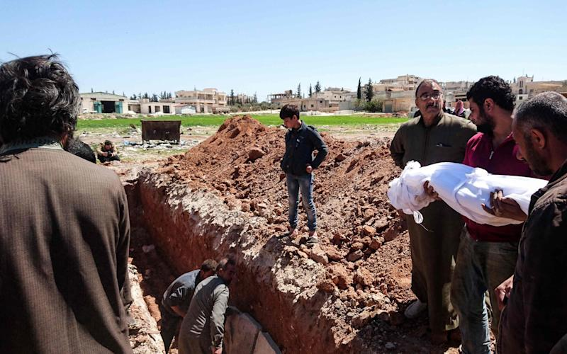 Syrians bury the bodies of victims of a a suspected toxic gas attack in Khan Sheikhun, a nearby rebel-held town in Syrias northwestern Idlib province - Credit: AFP
