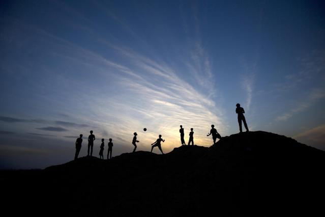A picture taken on May 4, 2014 at sunset shows Palestinian boys playing football in Beit Lahia in the northern Gaza Strip (AFP Photo/Mahmud Hams)