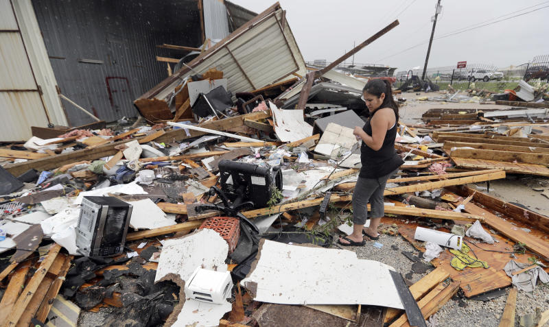 Jennifer Bryant looks over the debris from her family business destroyed by Hurricane Harvey Saturday, Aug. 26, 2017, in Katy, Texas.