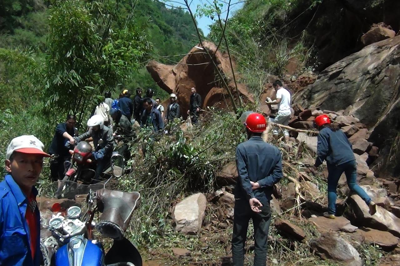 People try to get across a road blocked by a landslide following a powerful earthquake in Lushan county in southwest China's Sichuan province Saturday, April 20, 2013. The powerful earthquake shook China's Sichuan province Saturday morning, nearly five years after a devastating quake jolted the province. (AP Photo) CHINA OUT