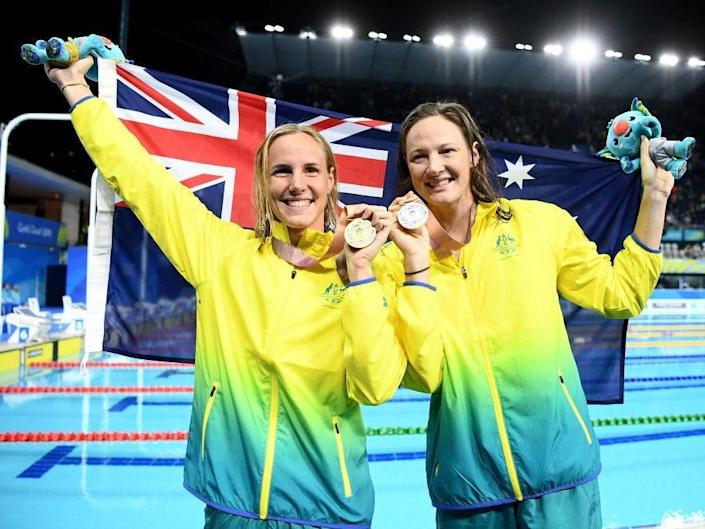 Swimmers Bronte and Cate Campbell hold an Australian flag after an event