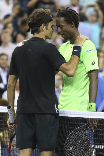 Gael Monfils, right, of France, meets at the net with Roger Federer, of Switzerland, after their quarterfinal at the U.S. Open tennis tournament, Thursday, Sept. 4, 2014, in New York. Federer won 4-6, 3-6, 6-4, 7-5, 6-2. (AP Photo/John Minchillo)
