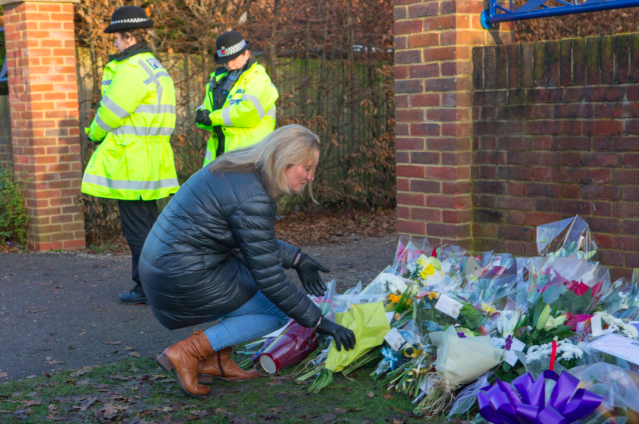 Tearful parents and pupils laid dozens of floral bouquets near the entrance to the school (PA)