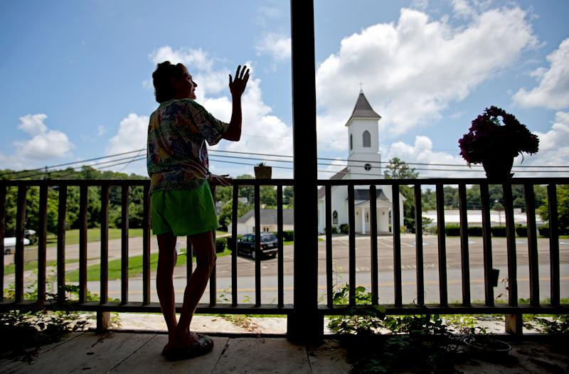 In this Tuesday, July 9, 2013 photo, Nanette Cooper stands on the front porch of the home she shares with her husband, Lawrence Cooper, in Nelson, Ga. The couple owns several guns and supports a recent city law requiring every head of household to own a gun and ammunition. As the national debate over gun control swirled in the spring, the tiny Georgia city made a statement supporting gun rights by passing an ordinance requiring gun ownership. Now a national gun control group is using a lawsuit challenging that law to send a message of its own. (AP Photo/David Goldman)