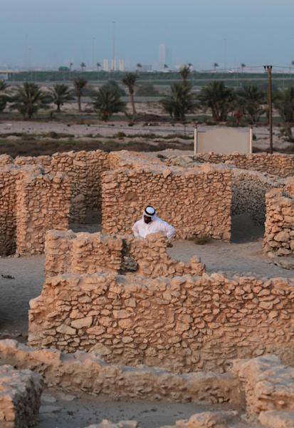 In this picture taken July 8, 2013, Bahraini archaeologist Abdul Aziz al-Suwailah stands in a Dilmun-era temple in Saar, Bahrain, in the heart of an expansive Bronze-age settlement. The settlement includes the temple, which was built in about 1900 BC and remained in use for 150 to 200 years, dwellings and a honeycomb-like graveyard that stretches up to a modern highway in northwestern Bahrain. (AP Photo/Hasan Jamali)