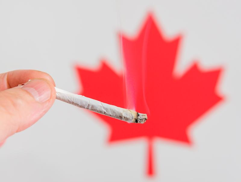 A lit cannabis joint being held in front of the red maple leaf of Canada's flag.