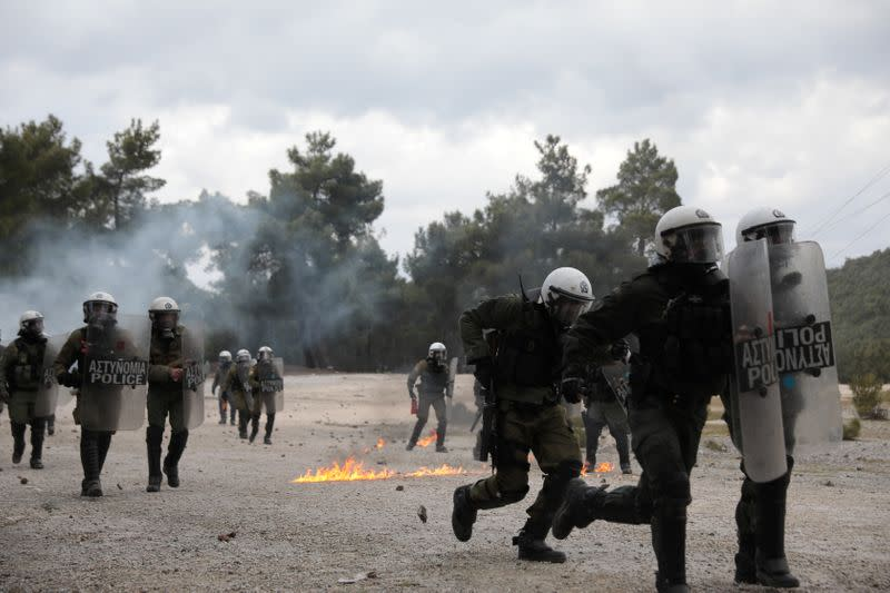Riot police charge at demonstrators who oppose the building of a new closed migrant detention centre during clashes in the area of Diavolorema on the island of Lesbos