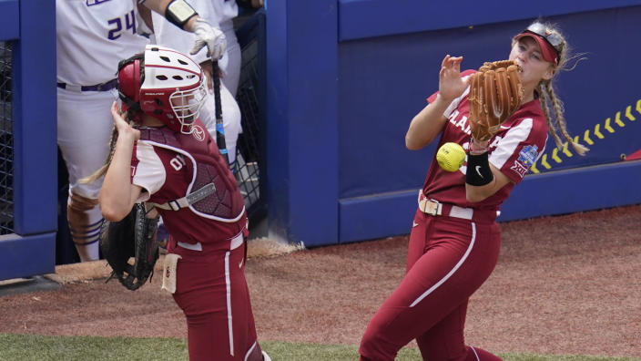 A foul ball hit by James Madison's Logan Newton falls between Oklahoma catcher Kinzie Hansen, left, and third baseman Jana Johns, right, in the seventh inning of an NCAA Women's College World Series softball game Sunday, June 6, 2021, in Oklahoma City. (AP Photo/Sue Ogrocki)